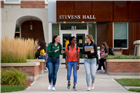 Three female students walking out of Stevens Hall